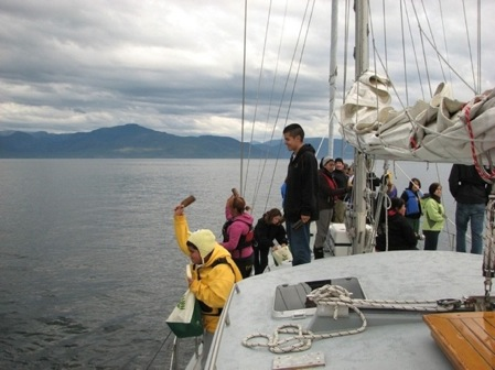 A young student on board Achiever throws a bottle with a message in it, into the waters of the Salish Sea.
