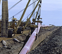 Heavy equipment lays an oil pipe in the ground