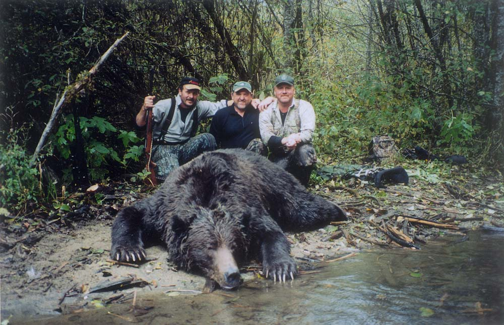 3 trophy hunters kneel behind a dead grizzly.