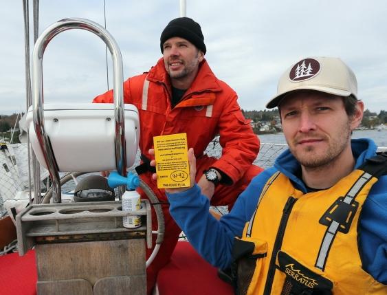 Raincoast researchers display drift cards aboard sailboat in the Salish Sea.