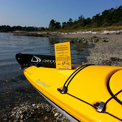 A drift card sits on a kayak hauled up on a beach
