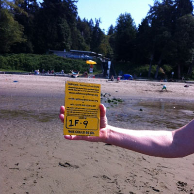 An arm holds a drift card in front of a public swimming beach