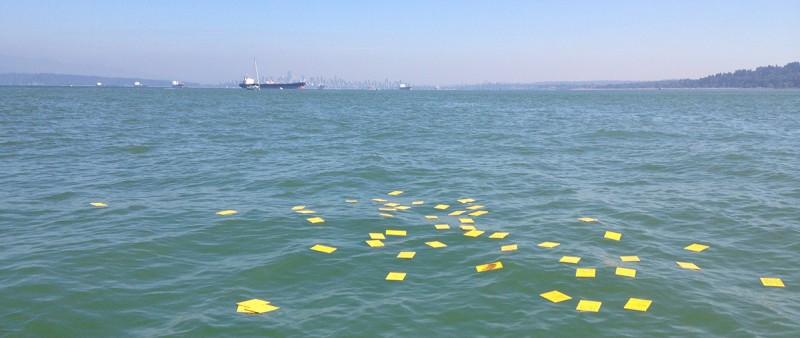 Drift cards float in the water with a tanker in the background