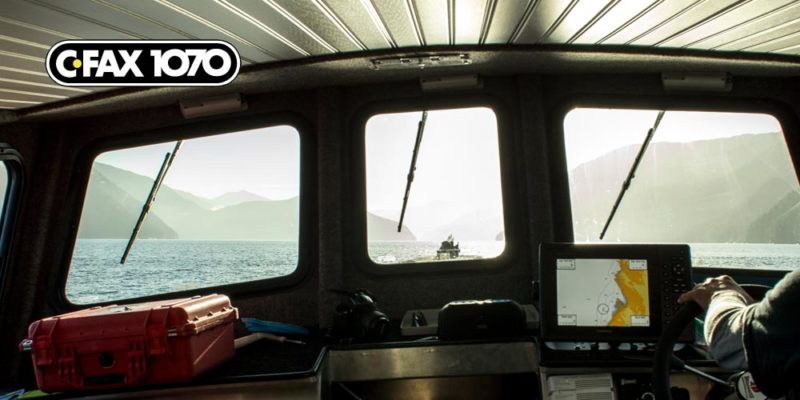 The view of the coast through the front window of a research vessel on the water.