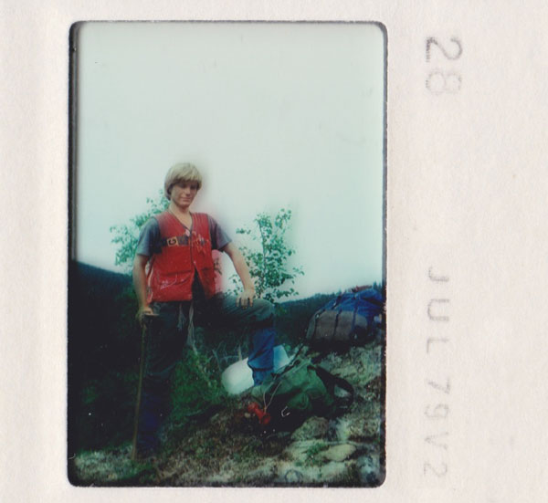 A young Matthew Sanger stands beside his gear, in the Yukon bush.