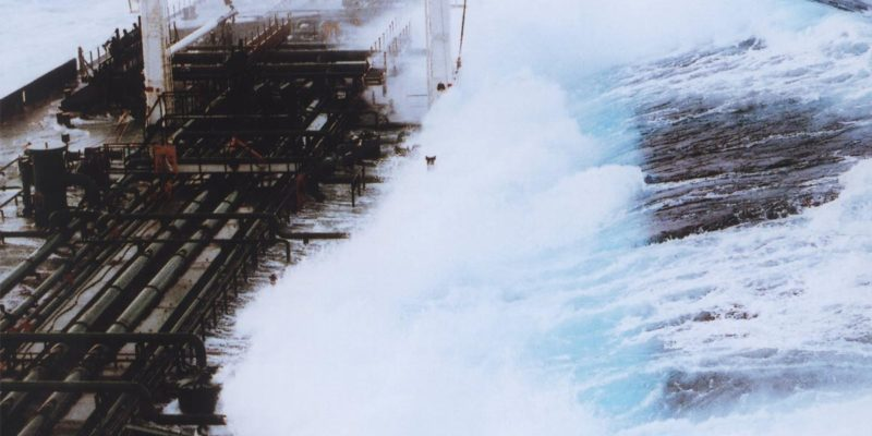 An oil tanker is hit by a wave in heavy seas.