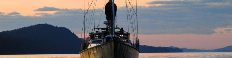 Achiever rests, sails down, in the twilight.