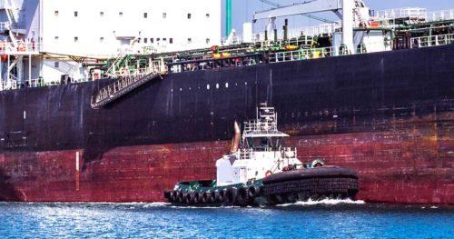 A tug lines up beside a massive oil tanker.
