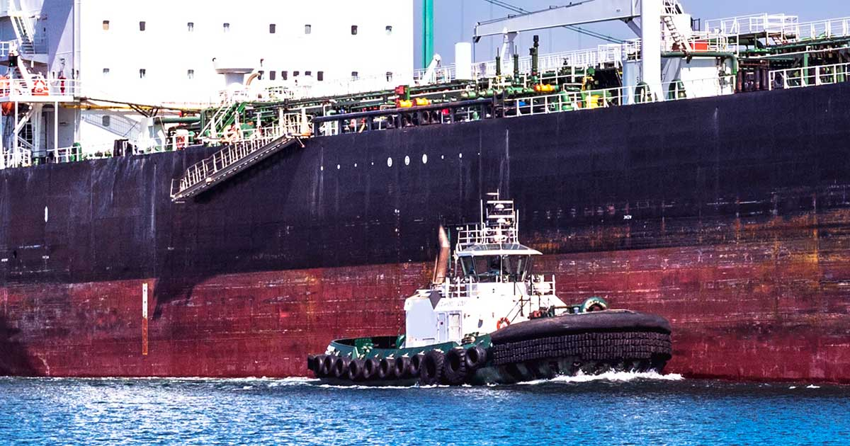 A tug lines up beside a massive oil tanker.