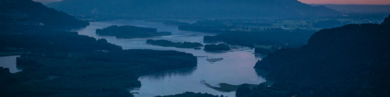 Dusk settles over the mountains and waters of the Fraser River watershed (aerial view).