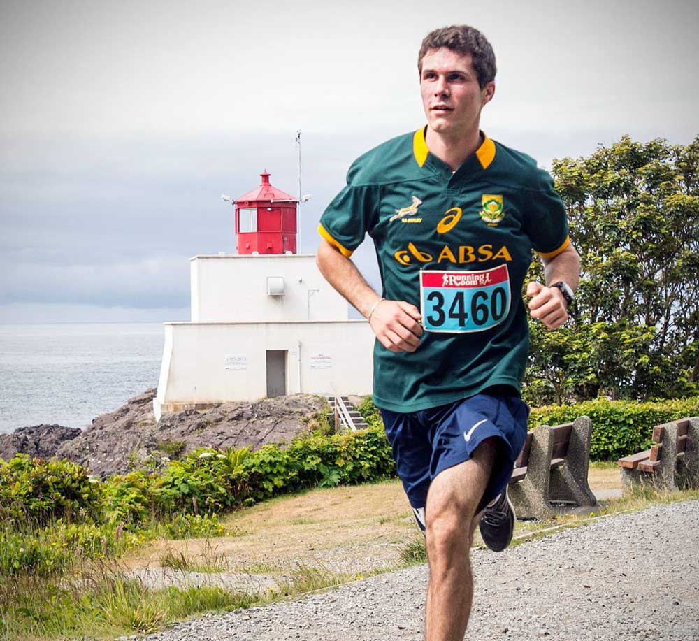 Gio runs by a lighthouse, during a Vancouver Island marathon.