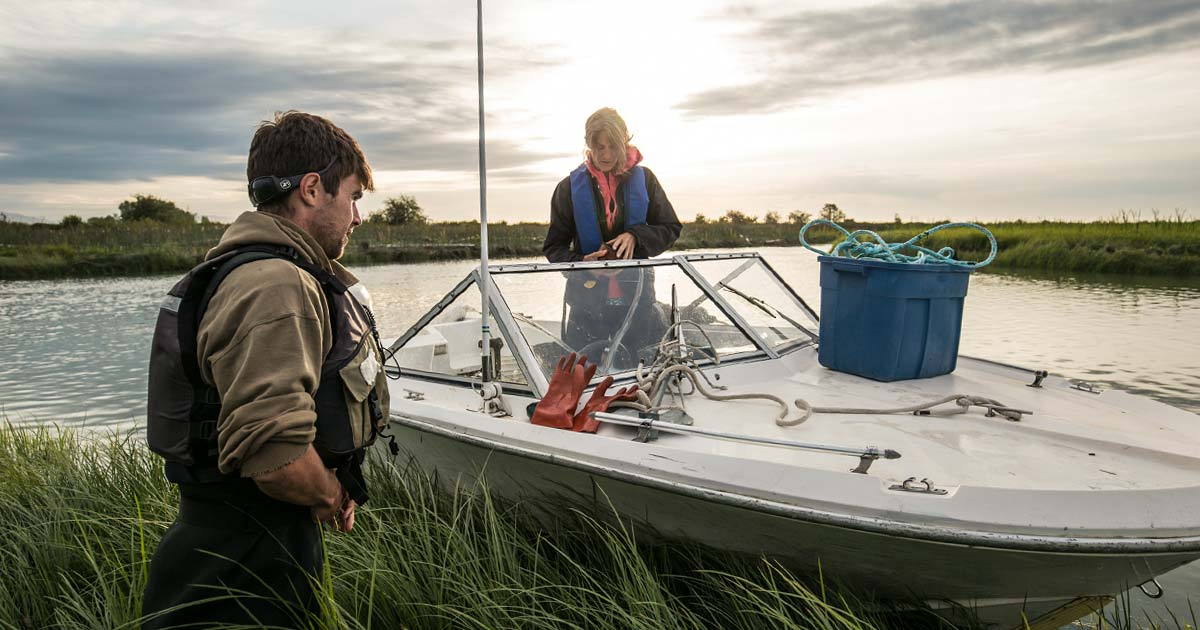 Misty MacDuffee and Dave Scott prepare gear on the motorboat in the Lower Fraser River.