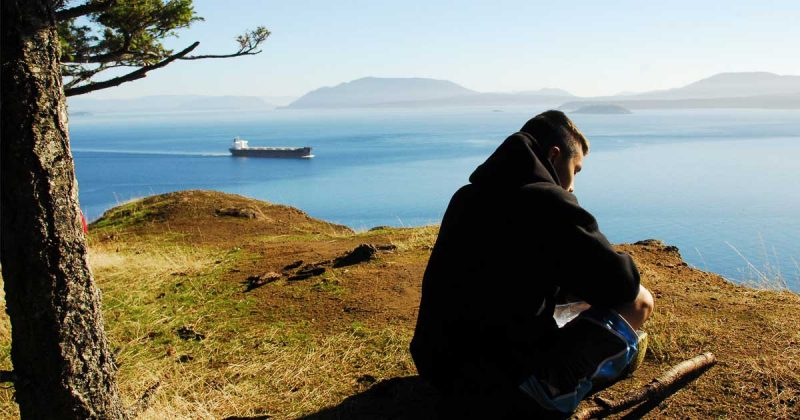 A youth participant of the Salish Sea Emerging Stewardship program has a solo sit at Monarch head for reflection and mindfulness.