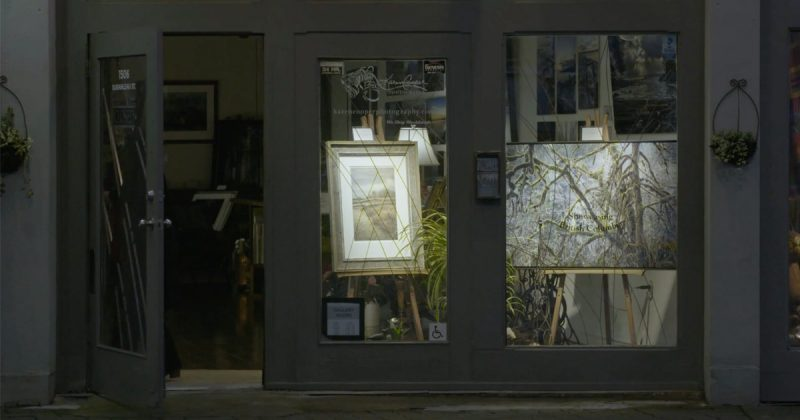 The warm interior lights and beautiful images of the Karen Cooper Gallery show through the evening darkness on Granville Island.