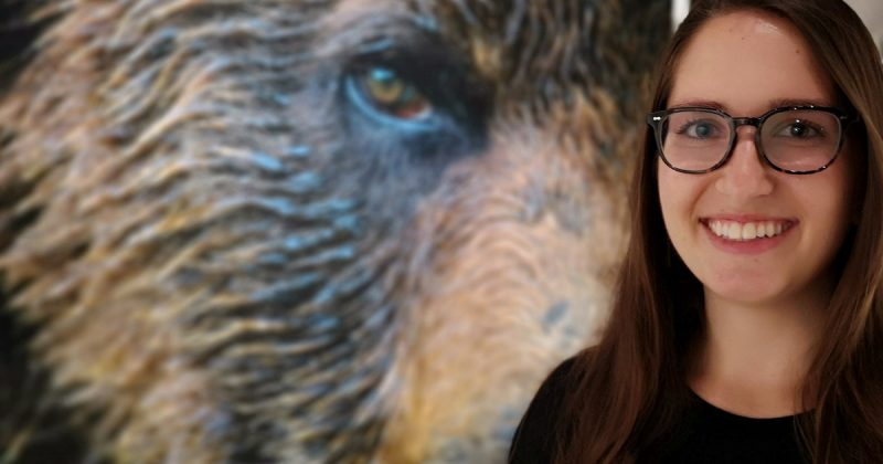Ilona Mihalik stands in front of an epic Grizzly bear photo as part of the One Shot for Coastal Carnivores exhibit.