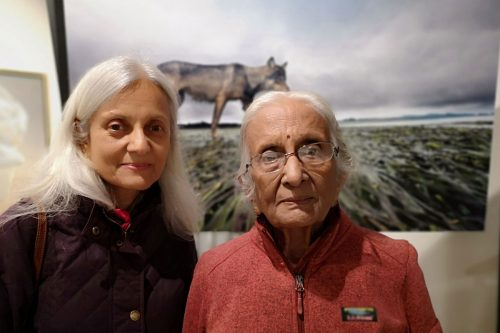 Two women pose in front of Bertie Gregory's photo at One Shot for Coastal Carnivores.