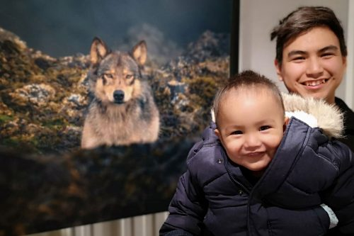 Father and son from Esquimalt nation pose in front of Cristina Mittermeier's photo at One Shot for Coastal Carnivores.