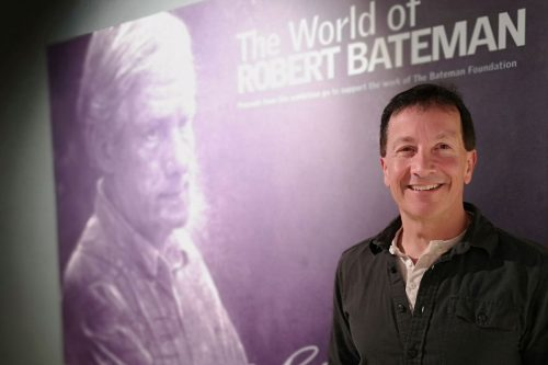 Chris Genovali poses in front of Robert Bateman wall at One Shot for Coastal Carnivores.