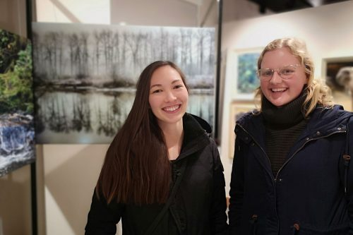 Two women stand in front of the One Shot for Coastal Carnivores exhibit at the Robert Bateman Centre.
