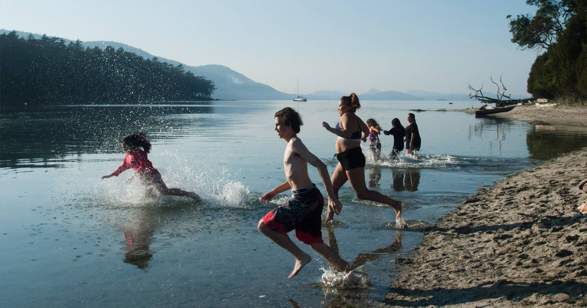 Students from the Salish Sea Emerging Stewards program race into the ocean from the beach.