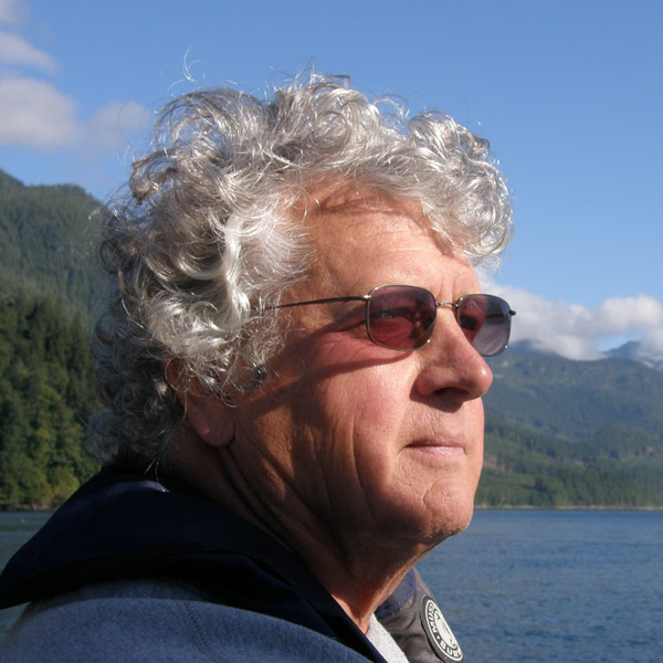 Fred Gregory wearing sunglasses, looking out over the ocean from a sailboat.