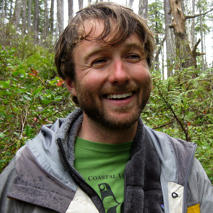 Kyle smiles widely, while standing in the rain in the west coast forest.