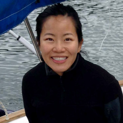 Maureen Vo stands on the bow of a small sailing vessel in the coastal waters of British Columbia.