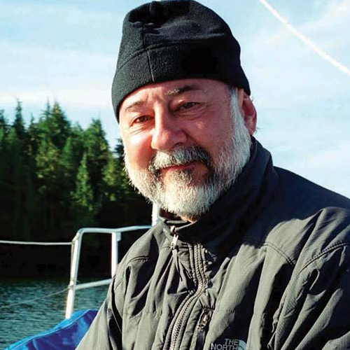 Paul Paquet, scientist, in his toque, on the bow of Achiever, smiling big time.