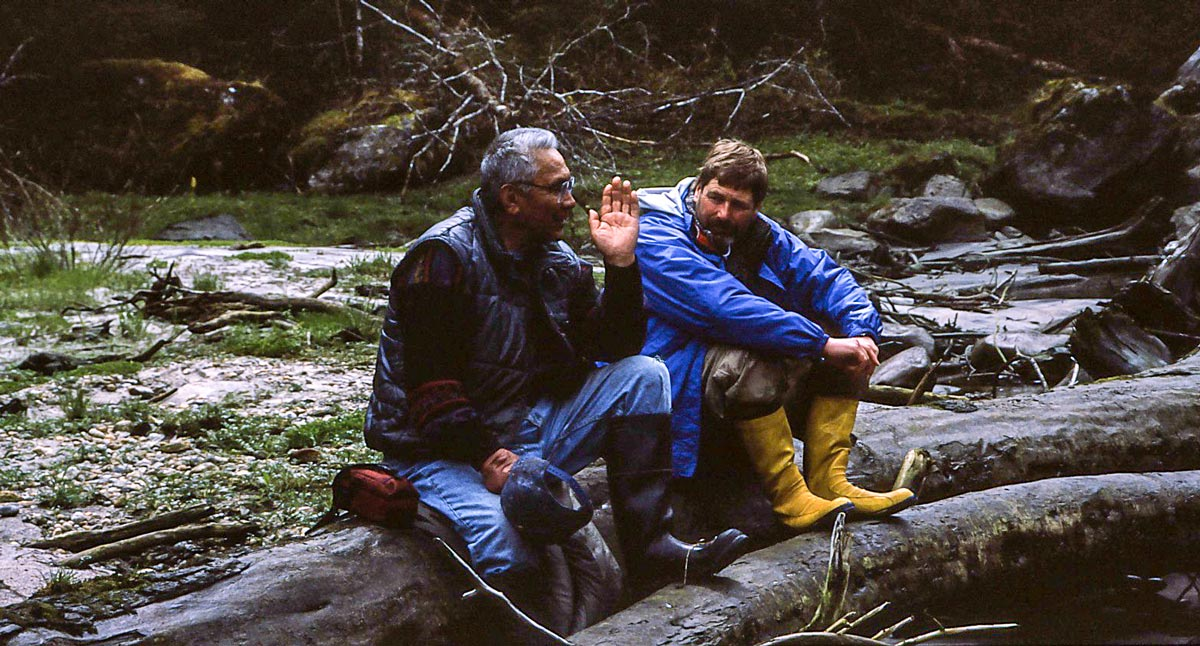 Cecil Paul and Brian Falconer sit on a river bank speaking about the Kitlope.