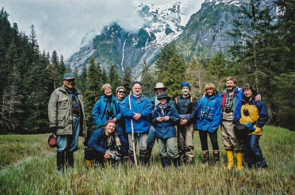 Cecil Paul and a group of Raincoasters and Maple Leafers stand in the open at the foot of mountains.