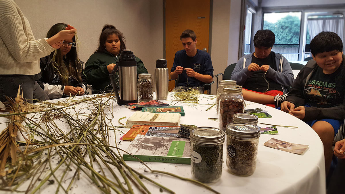 Students trying their hand at cordage weaving using stinging nettle.