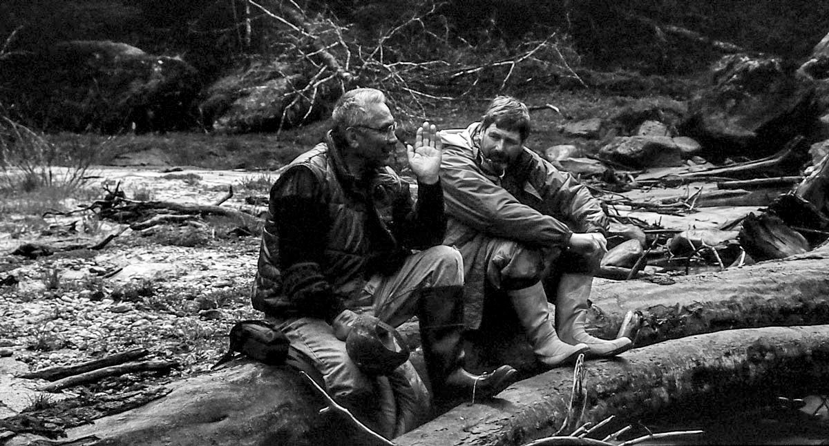 A black and white photograph of Cecil Paul and Brian Falconer sitting on a log by a river.