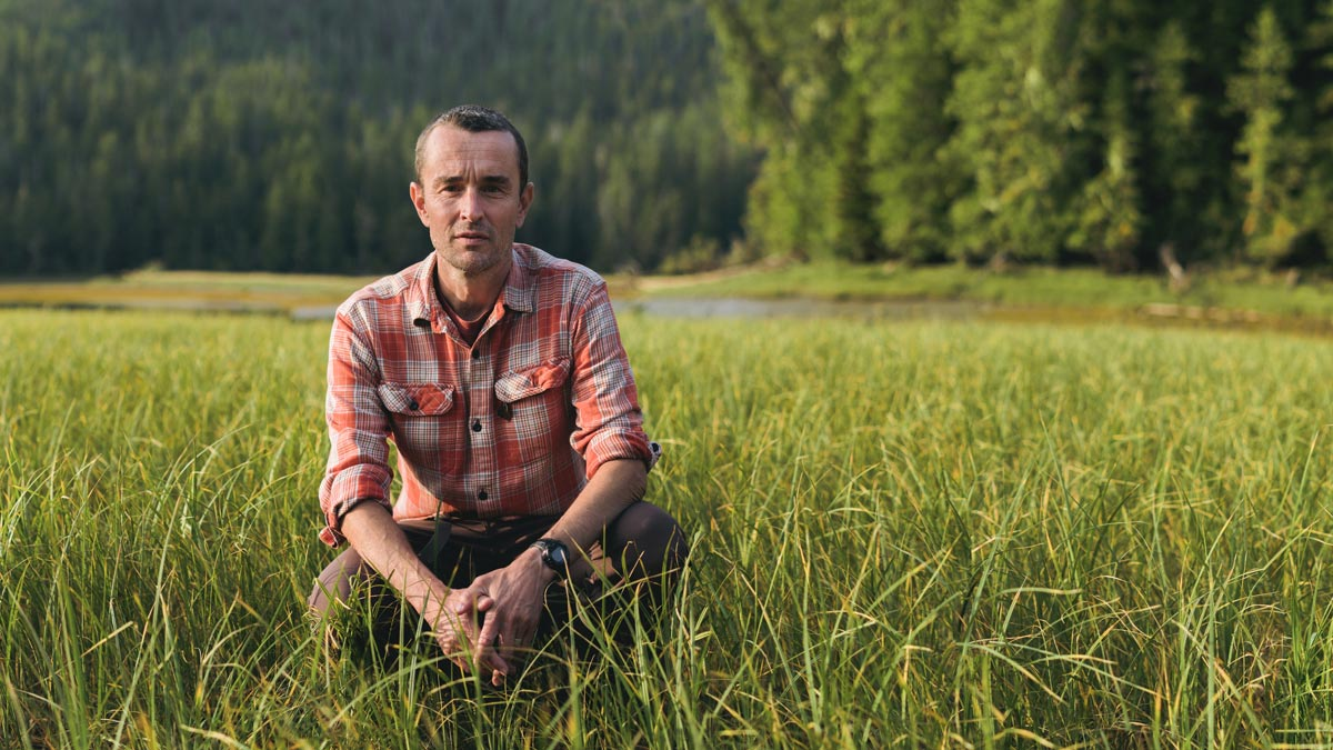 Chris Darimont crouching in tall grass wearing a plaid button up.