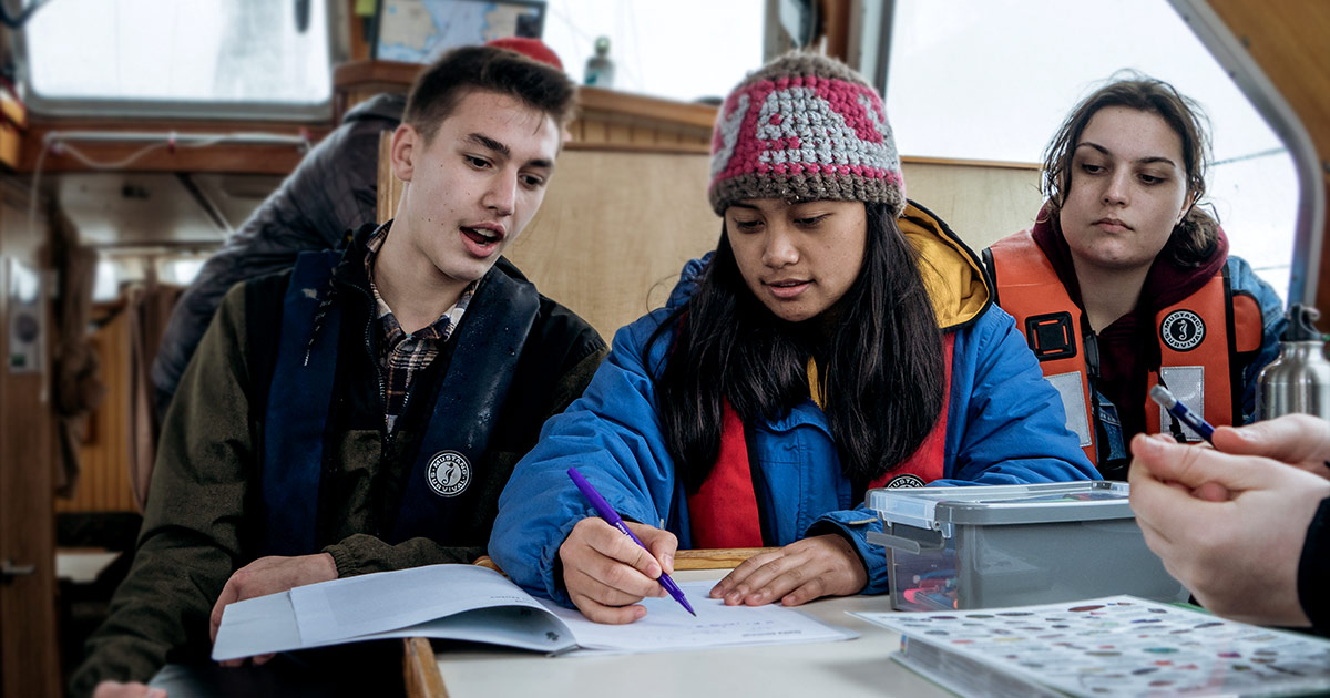 Youth leaders with the Salish Sea Emerging Stewards Program on the Achiever working on their charting and journal skills.