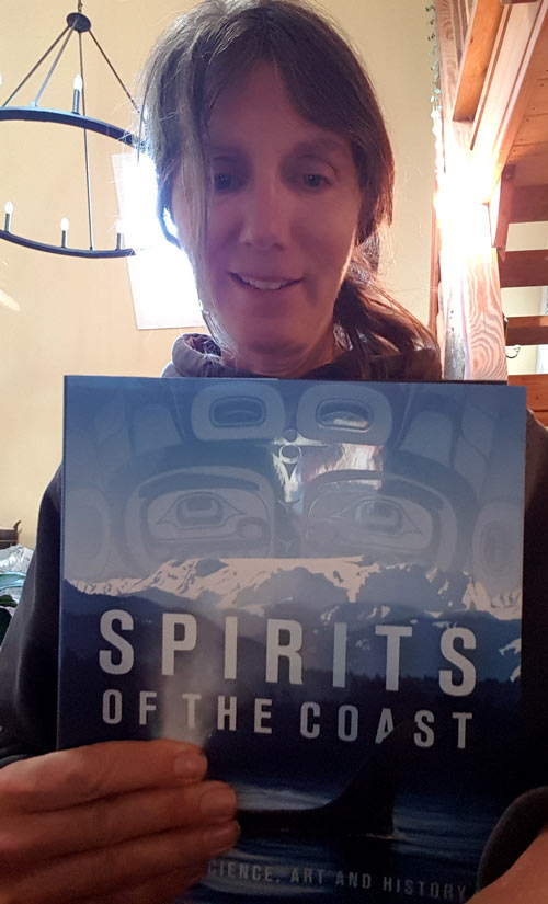 Misty MacDuffee holds up the book Spirits of the Coast.
