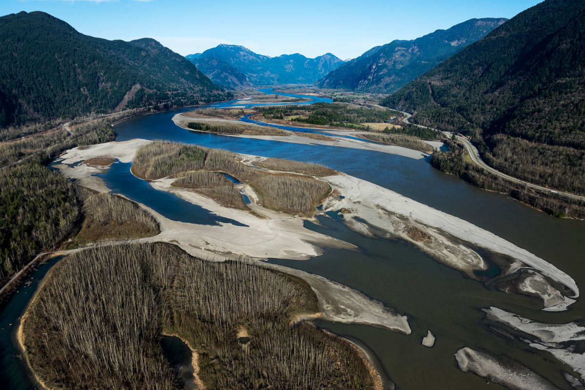 Aerial view of the interweaving eddies and regions of the Lower Fraser River nestled in the valley between mountains.