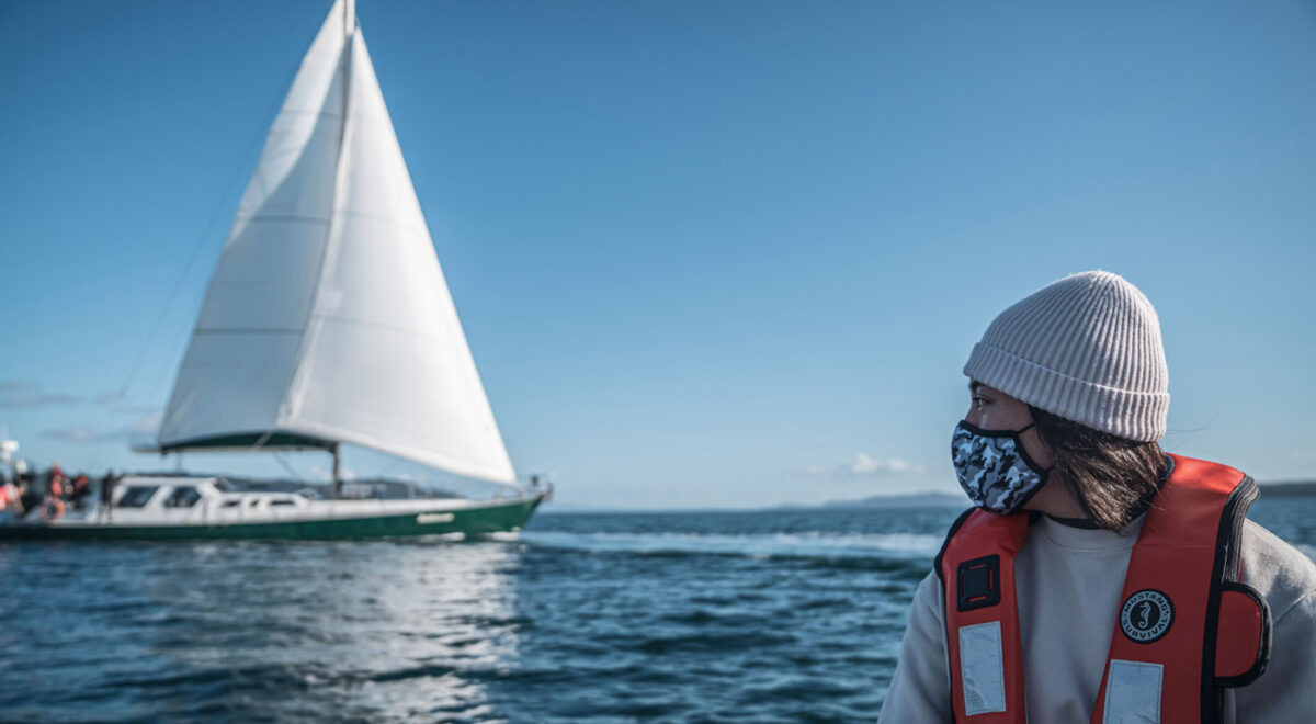 A Salish Sea emerging steward leader looks out at the Achiever from her boat.