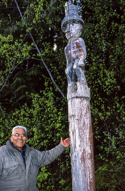 Cecil Paul at Kemano standing next to a totem pole.
