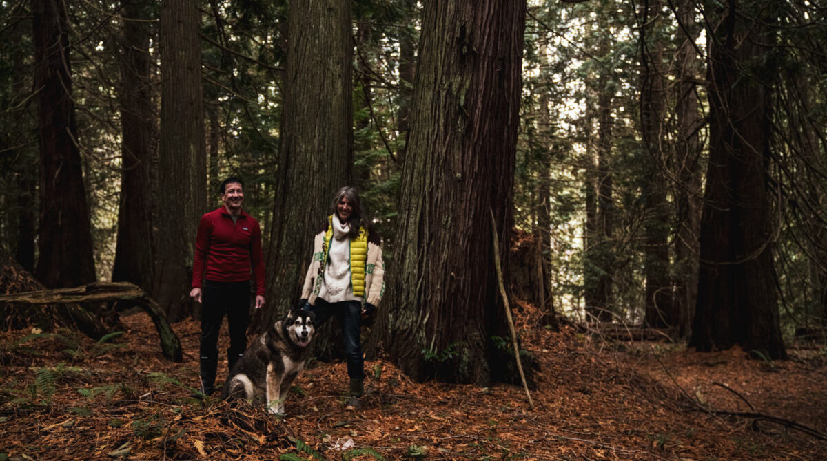 Chris, Misty, and Atticus stand among the giant trees in a forest on Pender Island.