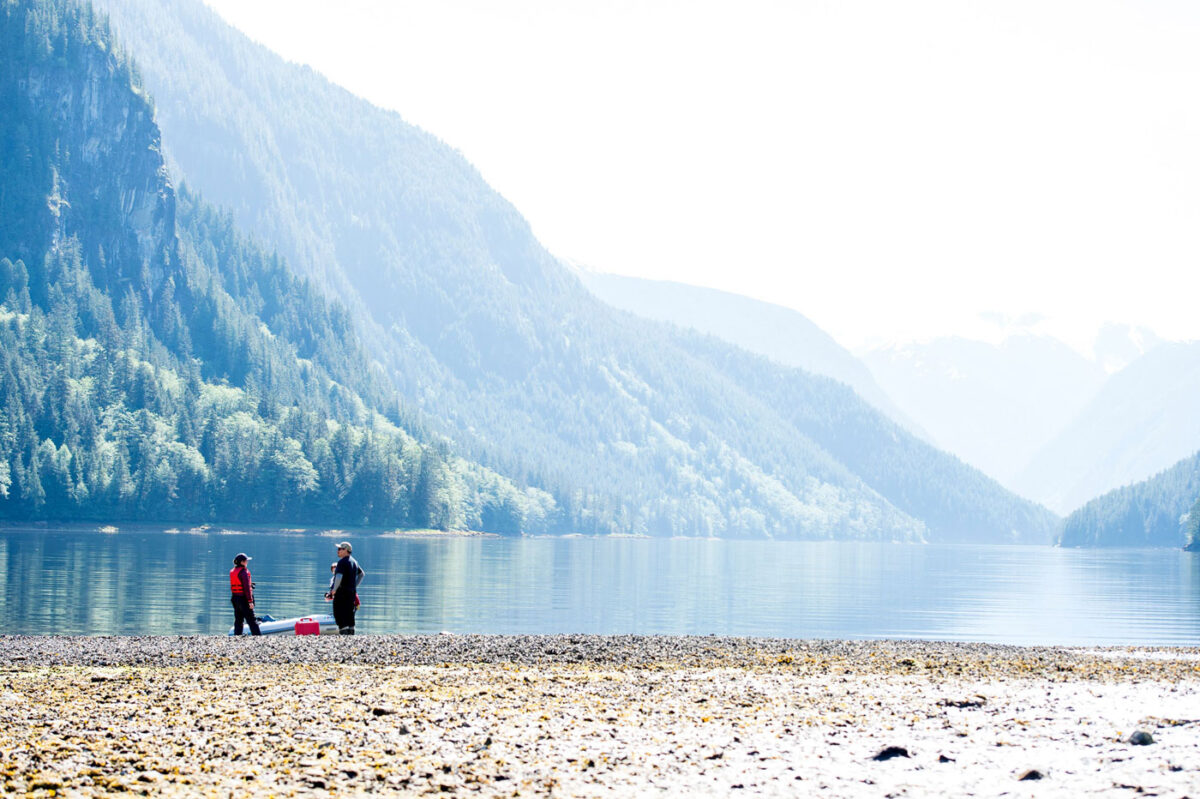 Two field researchers stand in the distance at the waters edge talking, with mountain forests looming in the background.