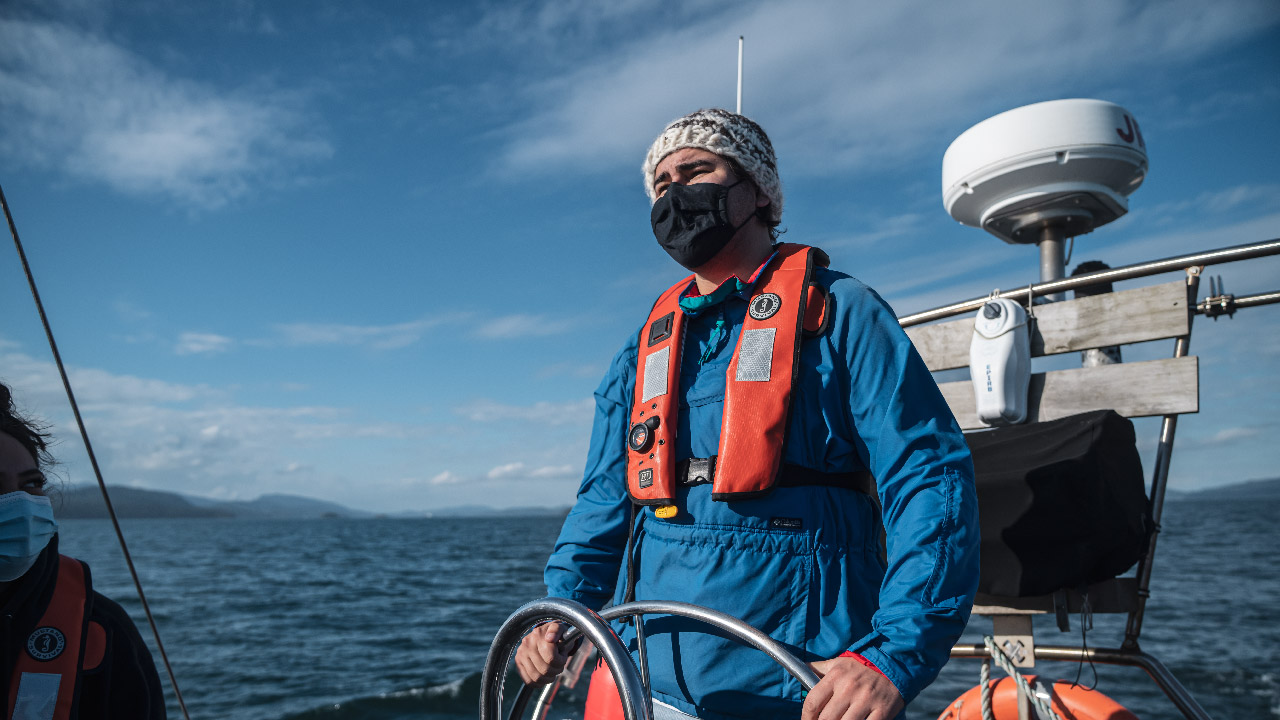 Peter Underwood steering Achiever with ocean and blue skies in the background
