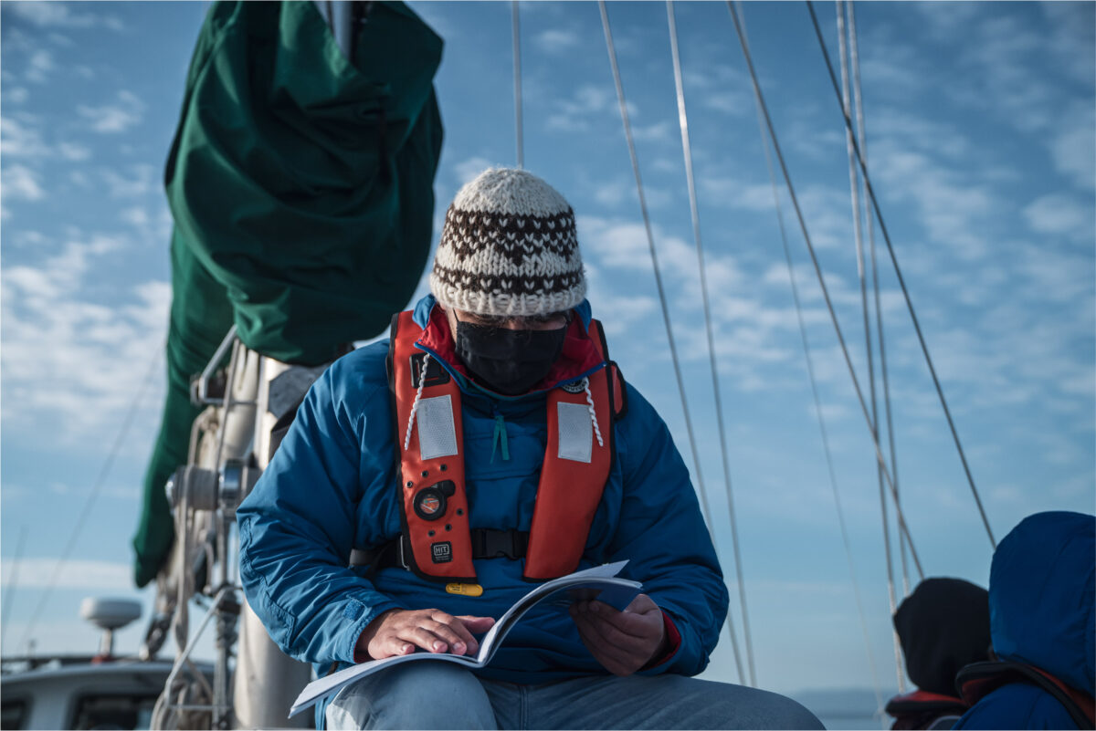 Peter Underwood reading Salt Water People (book) on deck of Achiever.