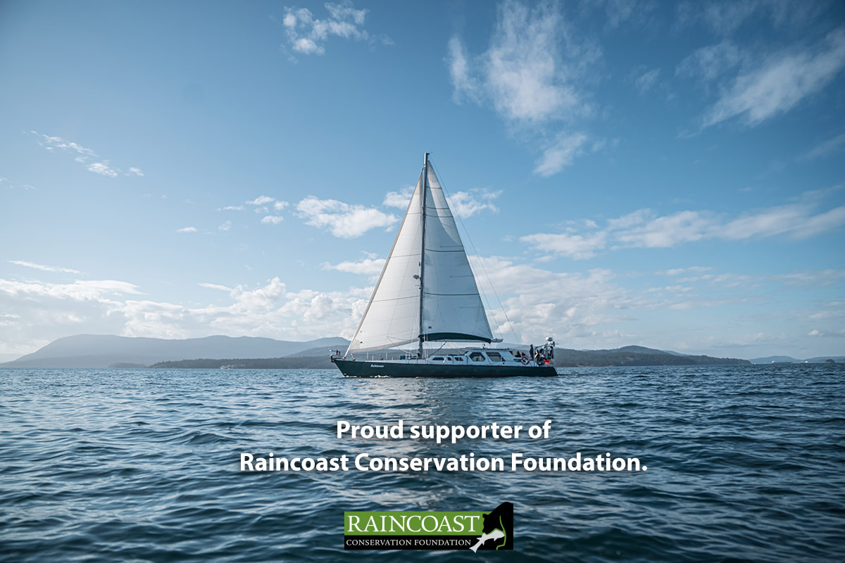 Achiever, the sailboat, with sails up on blue waters, with words below: Proud supporter of Raincoast Conservation Foundation.