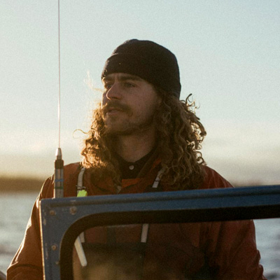 Drew Patrick Graham looks out over the windshield of a boat, wearing a toque and mustache.
