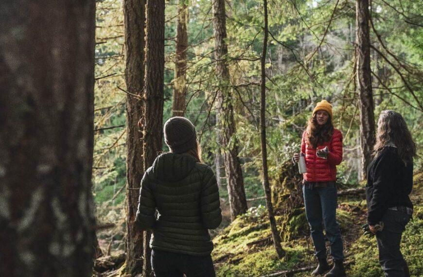 Three women standing 6 feet apart talking to each other in a Coastal Douglas-fir forest