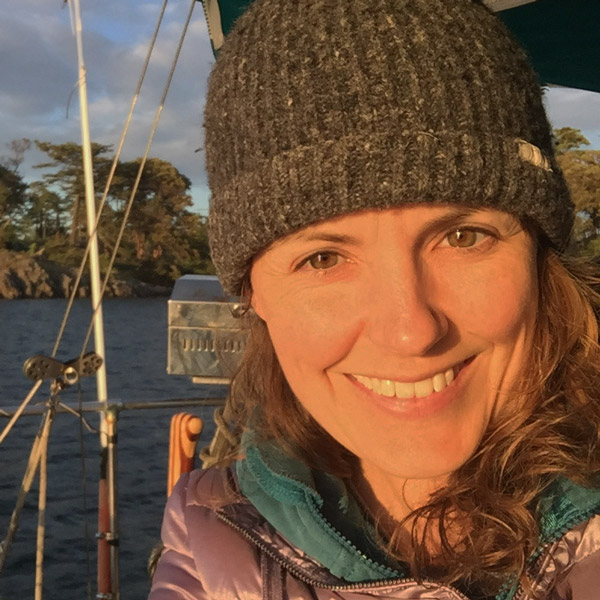 Asta Mail smiles into the light of the sunset on the waters of the Pacific, wearing a toque.