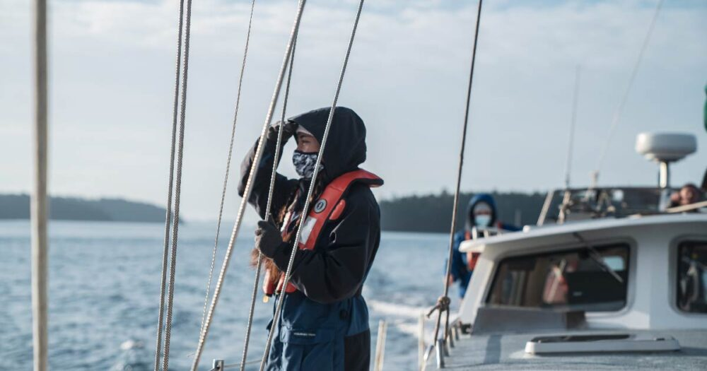 Young woman wearing a mask looking out at the ocean while standing on a sail boat.