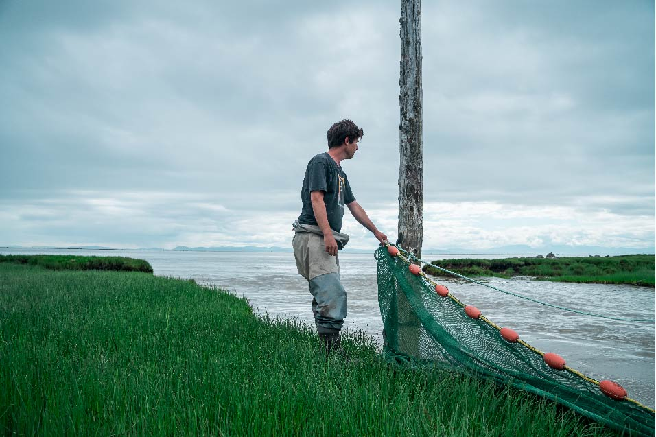 Dave Scott holds a net in the Fraser River Esutary on a cloudy day.