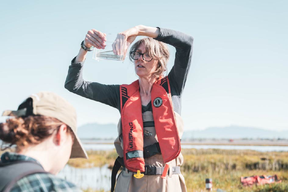 Misty MacDuffee looks at a salmon smolt in a viewfinder.