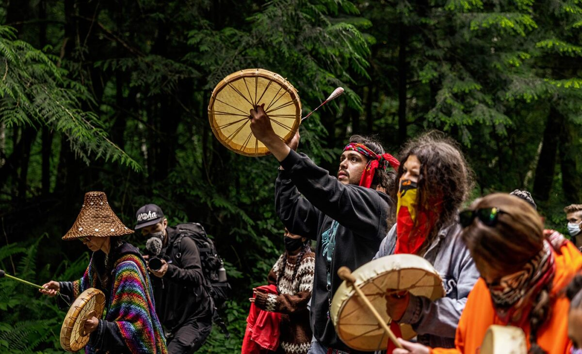 Indigenous people leading the walk with drums in hand.